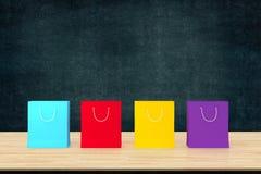 Kleurrijke het winkelen document zakken op houten lijst met zwarte raadsrug Royalty-vrije Stock Afbeelding