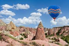 Kleurrijke hete luchtballon die over Rode vallei in Cappadocia, Turkije vliegen royalty-vrije stock foto's