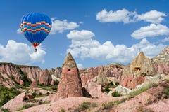 Kleurrijke hete luchtballon die over Rode vallei in Cappadocia, A vliegen stock fotografie