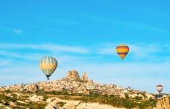 Kleurrijke hete luchtballons die dichtbij Uchisar-kasteel bij zonsopgang, Cappadocia, Turkije vliegen royalty-vrije stock fotografie