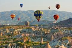 Kleurrijke hete luchtballons die over de vallei in Cappadocia vliegen Stock Foto