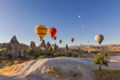 Kleurrijke hete luchtballons die over oude valleien vliegen Royalty-vrije Stock Foto