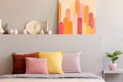Kleurrijke hoofdkussens op bed in grijs slaapkamerbinnenland met affiche en klok op bedhead Echte foto stock afbeelding