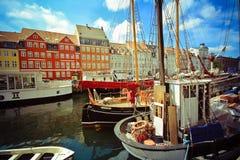 Kleurrijke huizen in de oude stad van Kopenhagen met boten en schepen in het kanaal voor hen Stock Foto's