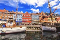 Kleurrijke huizen in de oude stad van Kopenhagen met boten en schepen in het kanaal voor hen Stock Afbeelding