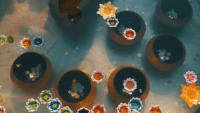 Kleurrijke Kaarsen in Lotus Shape Floating op Water in een Boeddhistische Tempel thailand stock video