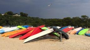 Kleurrijke Kajaks op Stormachtig Strand Stock Afbeeldingen