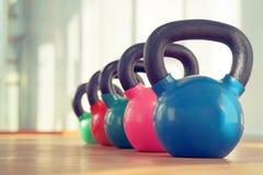 Kleurrijke kettlebells in gymnastiek Stock Foto