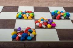 Kleurrijke kiezelstenen die op gecontroleerde raad worden uitgespreid Royalty-vrije Stock Foto