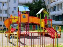 Kleurrijke kinderen` s speelplaats met dia's en schommeling in de binnenplaats van een woningbouw met meerdere verdiepingen stock fotografie