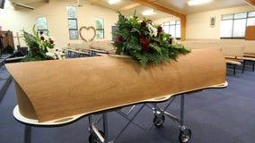 Kleurrijke kist in een lijkwagen of een kapel vóór begrafenis of begrafenis bij begraafplaats stock afbeeldingen