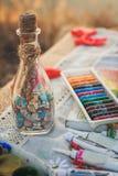 Kleurrijke kleurpotloden, acrylverven en fles met wensen Stock Foto's