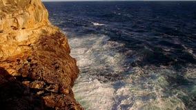 Kleurrijke klippenlijn met diep blauwe oceaan en brekende golven stock footage