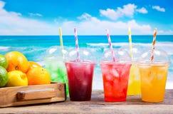 Kleurrijke koude dranken in plastic koppen op het strand royalty-vrije stock fotografie