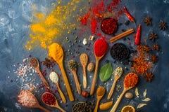 Kleurrijke kruiden in houten lepels, zaden, kruiden en noten op donkere steenlijst