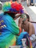 Kleurrijke kunstenaar die gezichtsverf voor kind doet, Stock Foto