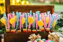 Kleurrijke lollys en verschillend gekleurd suikergoed op een houten doos stock foto