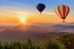 Kleurrijke luchtballonnen die over de berg met zonsopgang vliegen Stock Foto