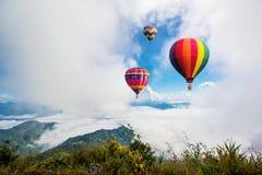 Kleurrijke luchtballonnen die over de berg vliegen Stock Afbeelding