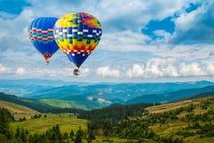 Kleurrijke luchtballonnen die over de bergen vliegen Artistiek pi Stock Afbeeldingen