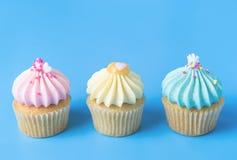 Kleurrijke luim drie cupcake op blauw royalty-vrije stock foto