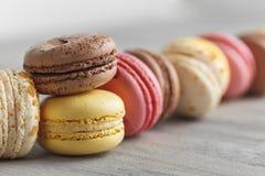 Kleurrijke makaroncakes op een rij over grijs royalty-vrije stock afbeeldingen