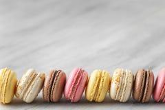 Kleurrijke makaroncakes op een rij over grijs royalty-vrije stock fotografie