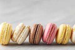 Kleurrijke makaroncakes op een rij over grijs stock foto