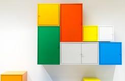 Kleurrijke metaalkabinetten die op witte muur hangen Royalty-vrije Stock Foto's