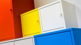 Kleurrijke metaalkabinetten die op witte muur hangen Royalty-vrije Stock Foto