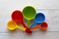 Kleurrijke metende lepels voor keuken op een witte houten backgrou Stock Foto