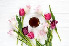 Kleurrijke mooie tulpen en koffiekop op de witte houten lijst Valentijnskaarten, de lenteachtergrond Bloemenspot omhoog royalty-vrije stock afbeeldingen