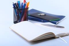 Kleurrijke notitieboekjes en bureaulevering op witte lijst royalty-vrije stock fotografie