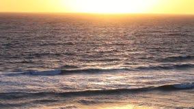 Kleurrijke oceaanwaterspiegel met branding tijdens zonsopgang stock video