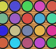 Kleurrijke oogschaduw in zwarte dozen over houten lijst Stock Foto's