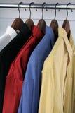 Kleurrijke overhemden op houten hangers Royalty-vrije Stock Afbeeldingen