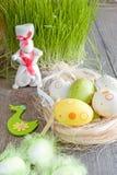 Kleurrijke paaseieren die op de lijst naast green van vers gras en het witte konijn liggen Stock Afbeelding
