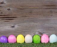 Kleurrijke paaseieren die op gras met rustieke houten backgro rusten Royalty-vrije Stock Afbeelding