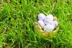 Kleurrijke paaseieren in een mand in het gras Stock Afbeelding