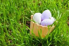 Kleurrijke paaseieren in een mand in het gras Royalty-vrije Stock Afbeelding
