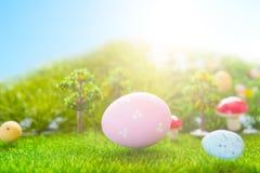 Kleurrijke paaseieren en één groot roze paasei op de lente groen gras royalty-vrije stock afbeeldingen