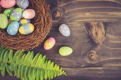 Kleurrijke paaseieren in keurig en groen blad op plank houten rug stock fotografie
