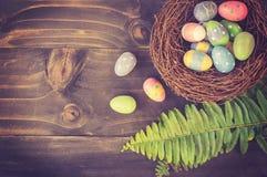 Kleurrijke paaseieren in keurig en groen blad op plank houten rug royalty-vrije stock afbeelding