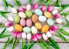 Kleurrijke paaseieren met cirkel van Tulpen op rustieke witte woode Royalty-vrije Stock Fotografie