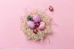 Kleurrijke paaseieren in nest op roze achtergrond Pasen-textuur royalty-vrije stock afbeelding
