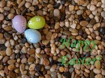 Kleurrijke paaseieren op bed van strandkiezelstenen met Gelukkige Pasen-groet Royalty-vrije Stock Afbeelding