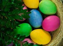 Kleurrijke paaseieren op hooi in de rieten mand Stock Afbeeldingen