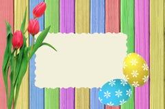 Kleurrijke paaseieren, roze tulpen en prentbriefkaar op geschilderde kleur Stock Afbeeldingen