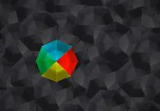Kleurrijke paraplu en vele zwarte paraplu's stock foto's