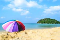 Kleurrijke paraplu met strand en blauwe hemelachtergrond Stock Foto